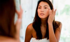 Donna allo specchio a criticare il corpo
